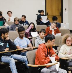 Students talk in pairs in a small lecture hall.
