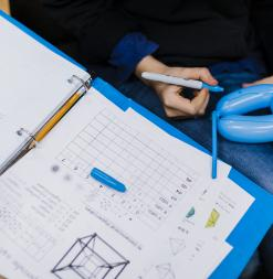 A student uses a pen to write on a balloon during a 3-dimensional object activity.