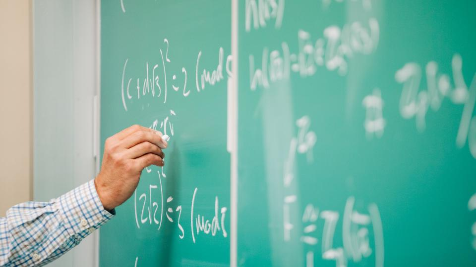 An instructor writes mathematics formulas on a green chalkboard.